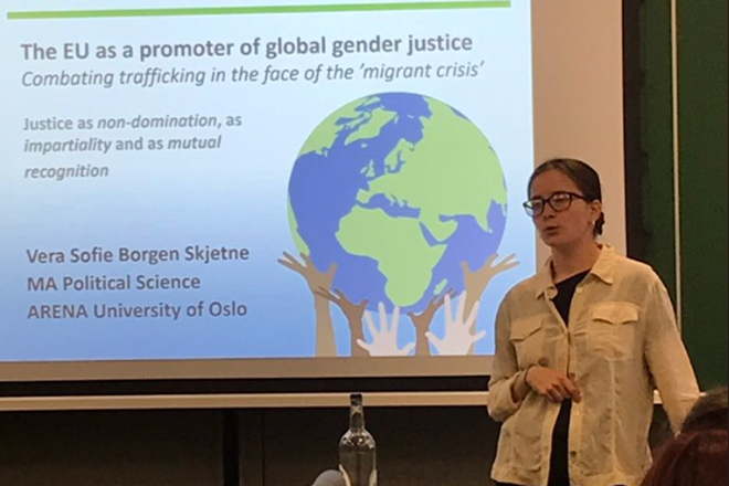 Woman presenting research on the EU as a a promoter of global gender justice, in front of screen in classroom